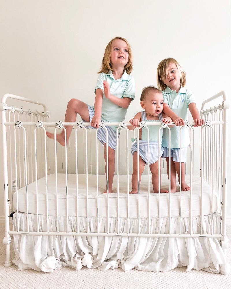 three little boys standing in crib