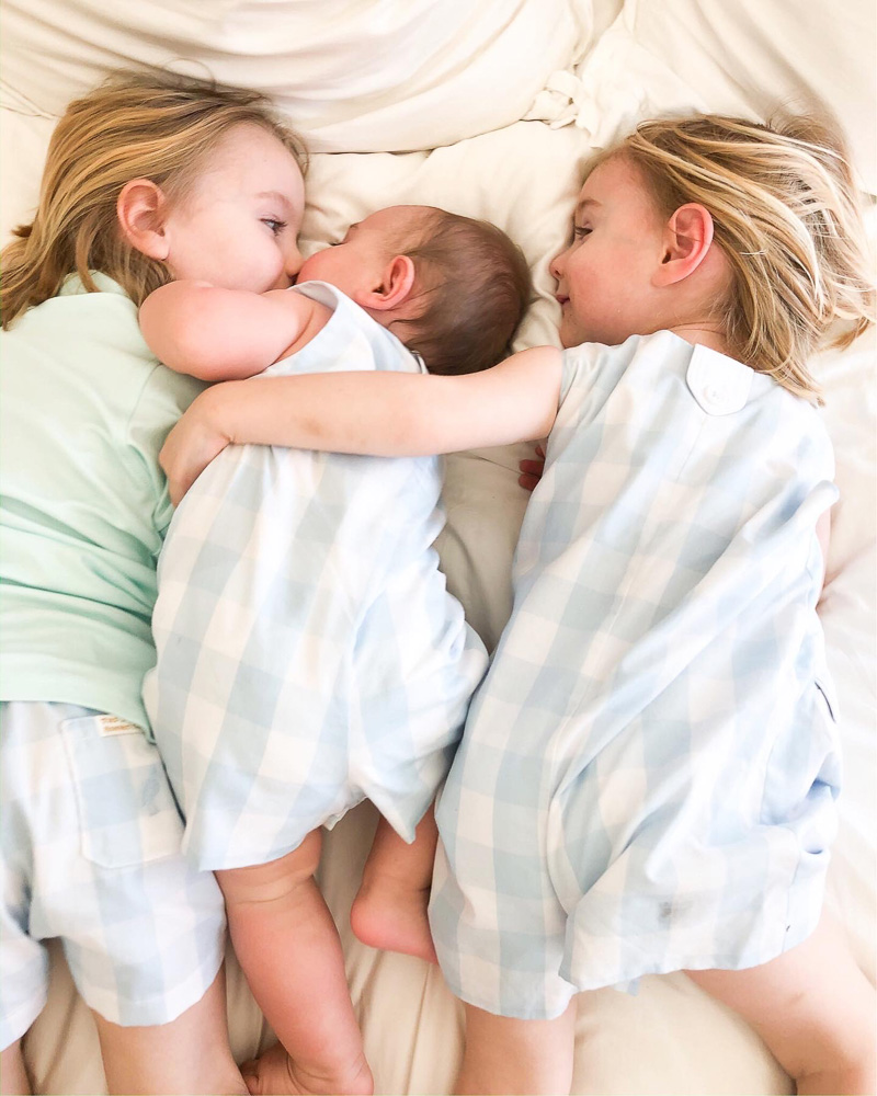 three little brothers snuggling in bed