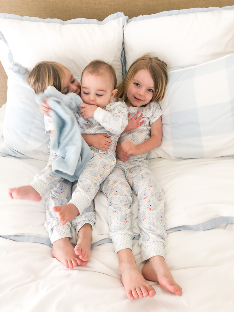 three toddler brothers snuggling in bed