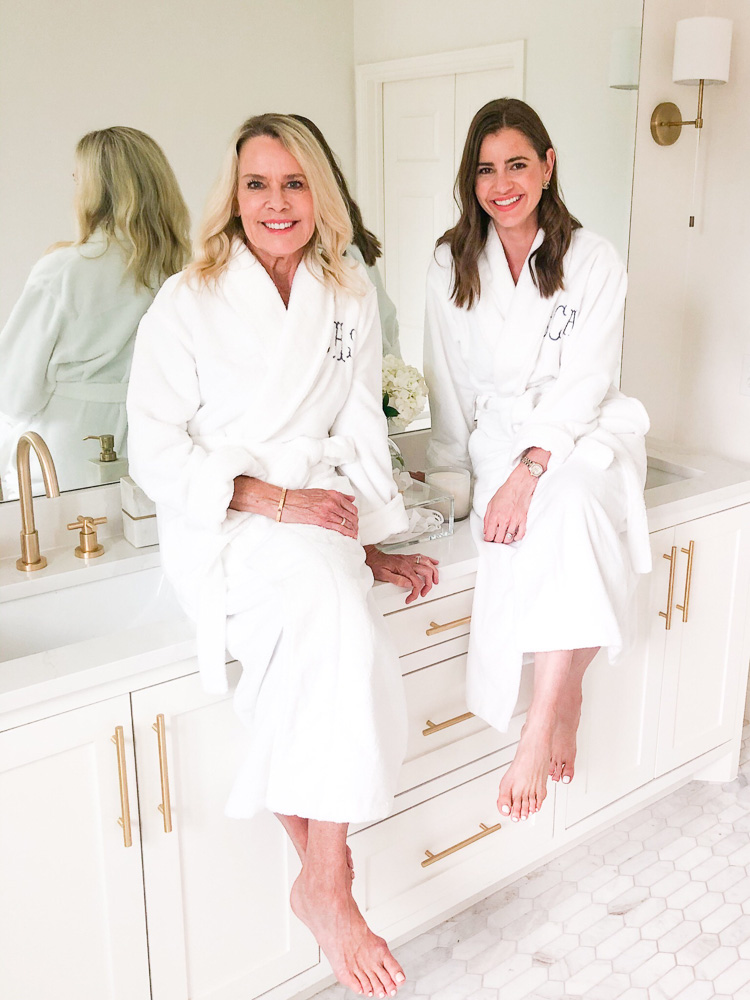 two women sitting on bathroom counter in spa robes