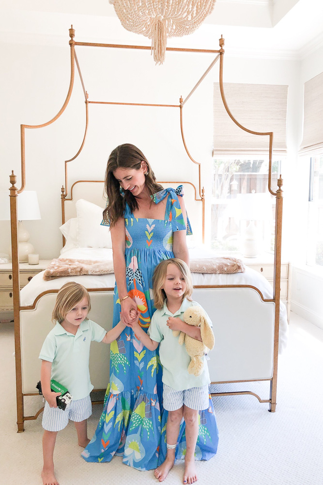 mom with two toddler boys standing by canopy bed