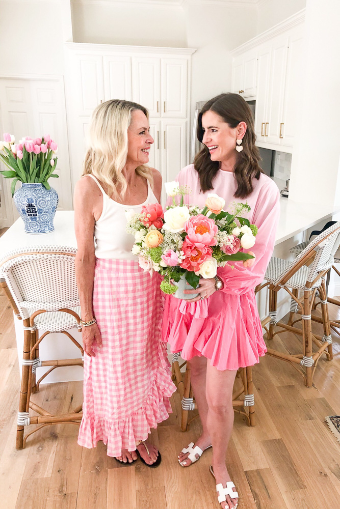 two women wearing pink holding a bouquet of flowers