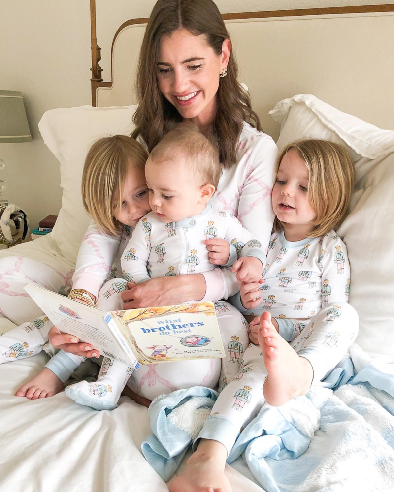 mom reading in bed to baby and two toddler boys