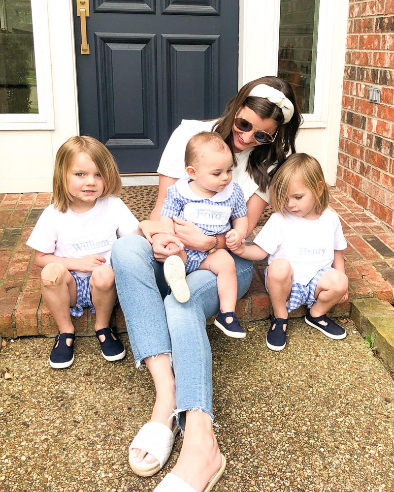mom sitting on front porch holding baby with two toddlers