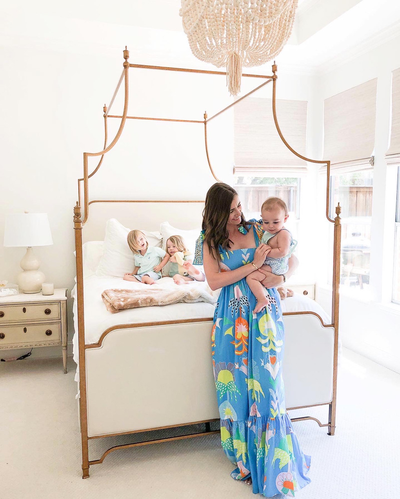 mom holding baby in front of canopy bed