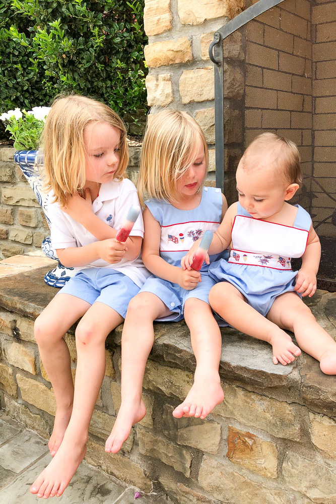 three little boys eating popsicles outside