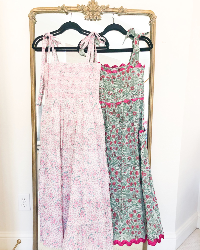two floral maxi dresses hanging on mirror