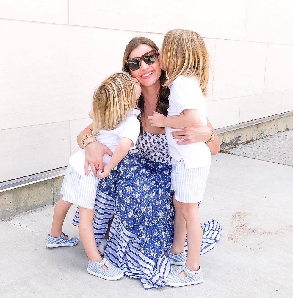 toddler boys kissing mom on her cheeks