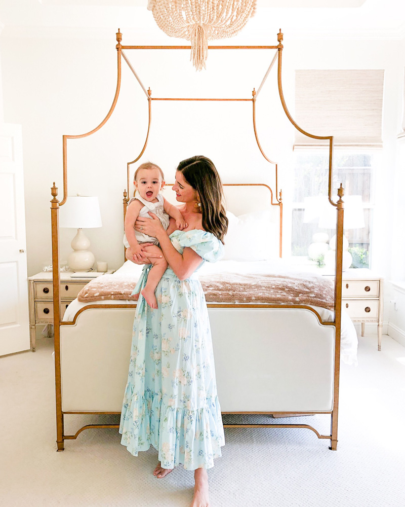 mom and baby standing by canopy bed