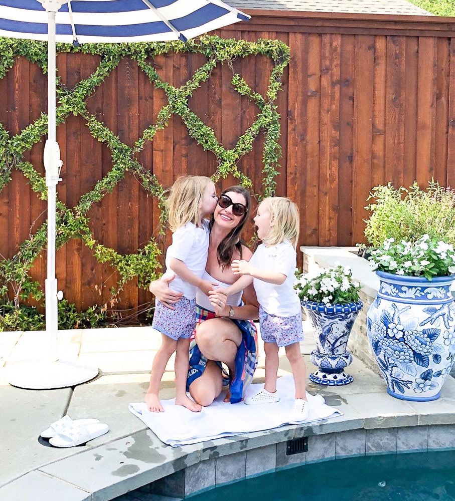 mom with two toddler boys by swimming pool