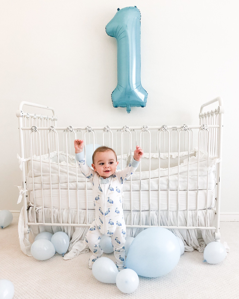 "baby boy on floor by crib withe ""1"" balloon"