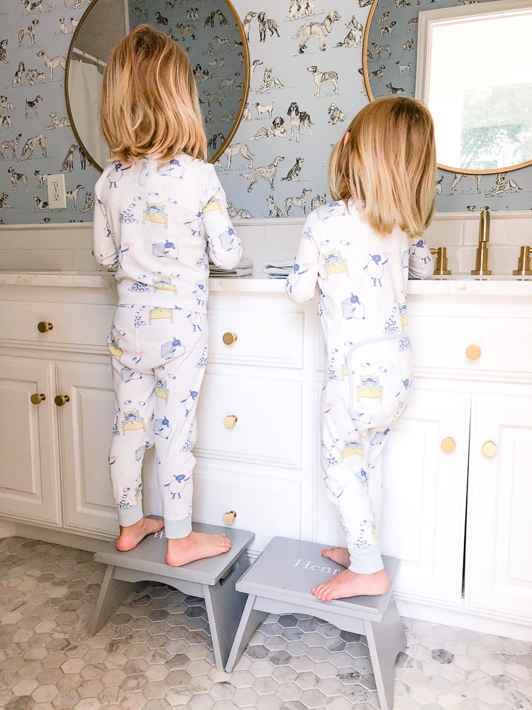 two toddler boys on stools at bathroom sink