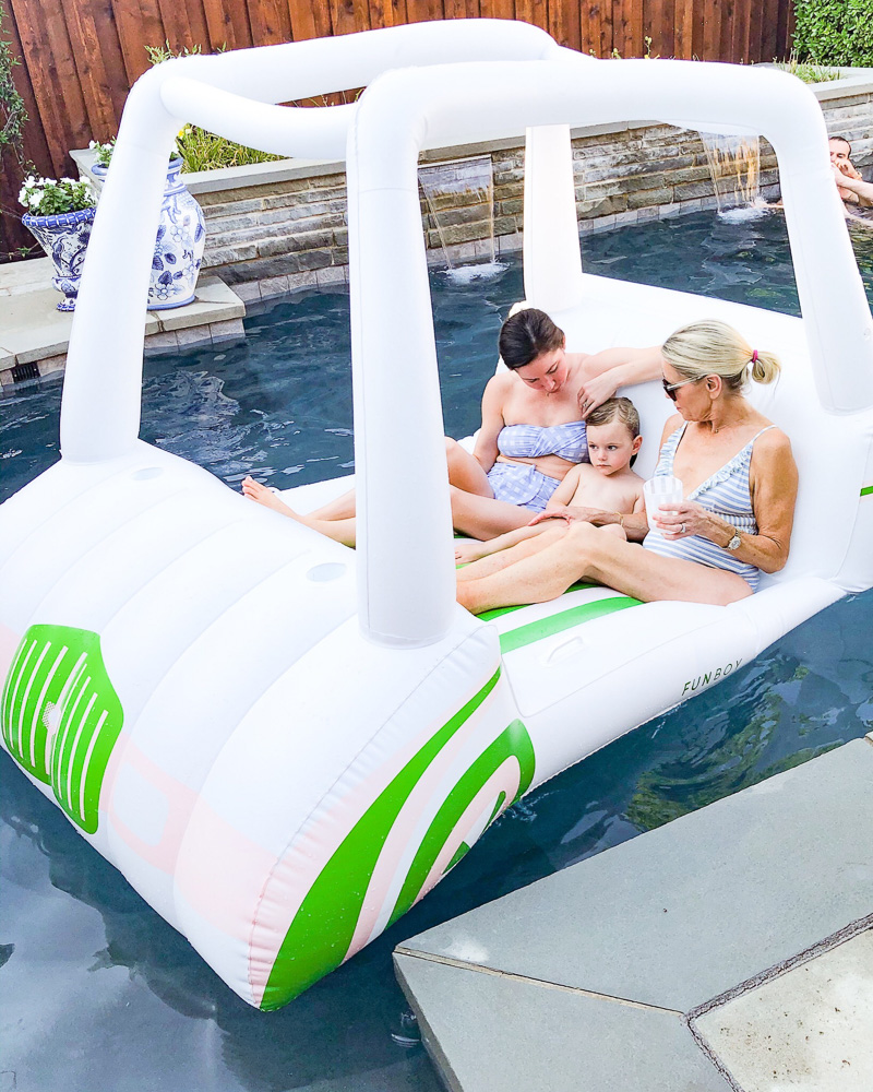 two women in golf cart pool float with toddler boy