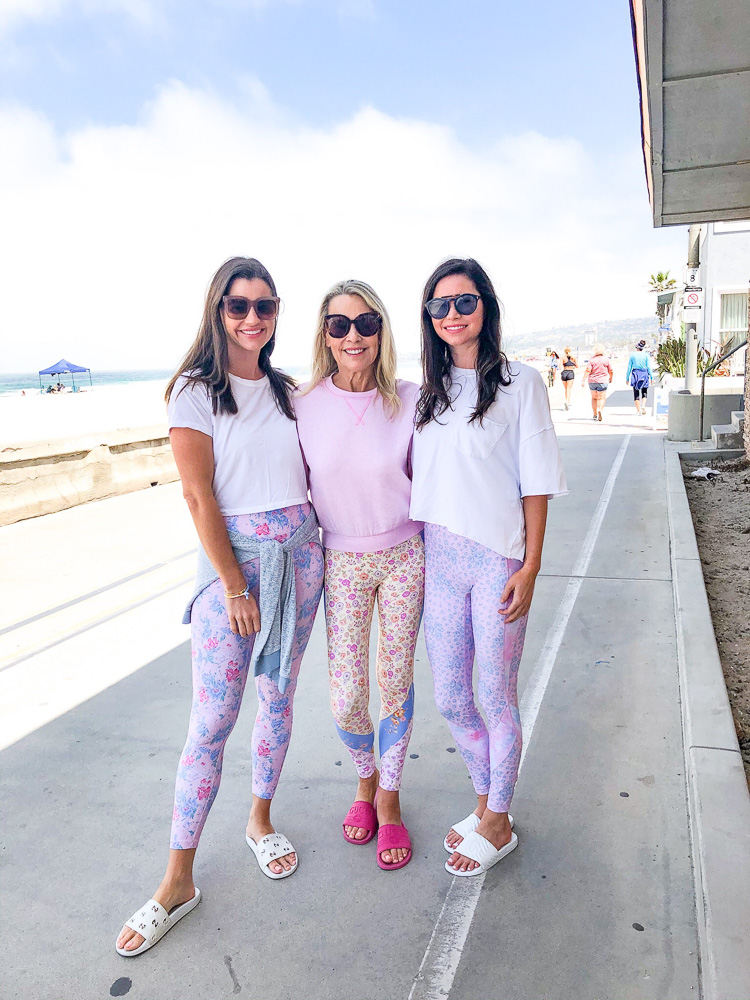 three women in athletic wear on the boardwalk