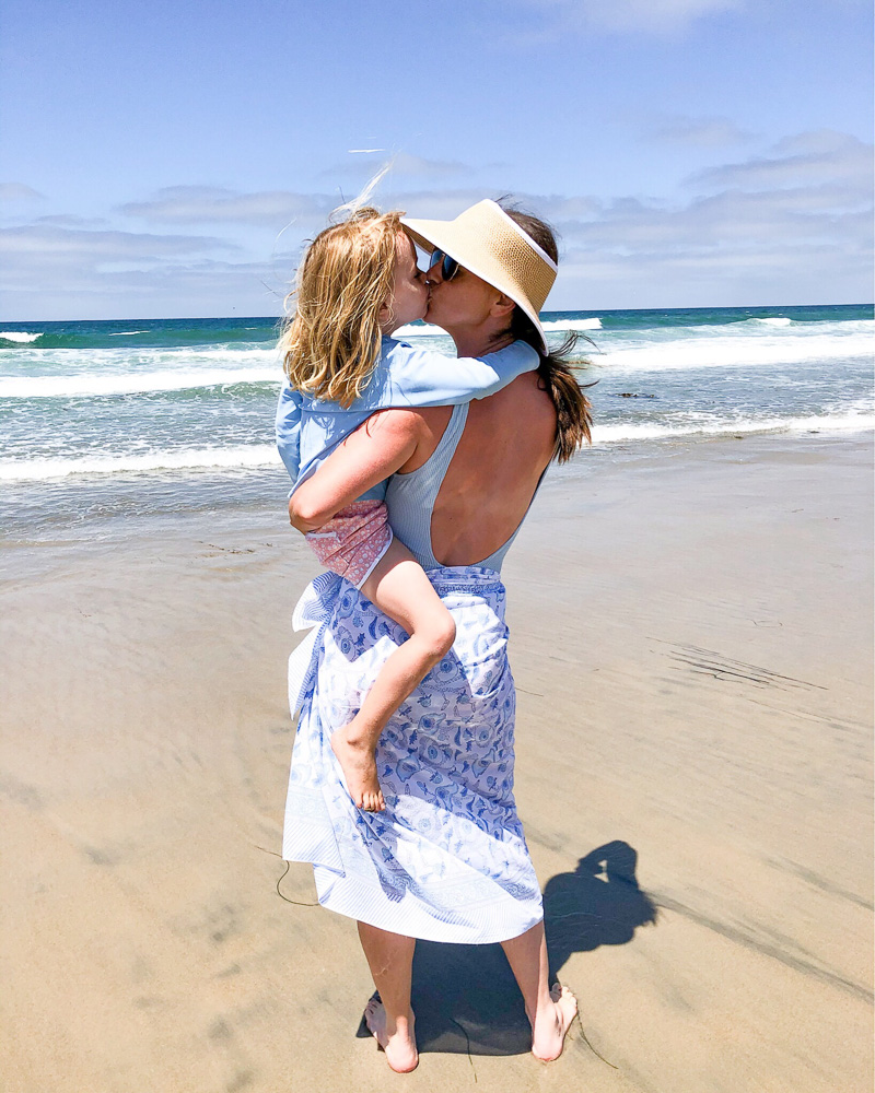 mom and toddler kissing on the beach