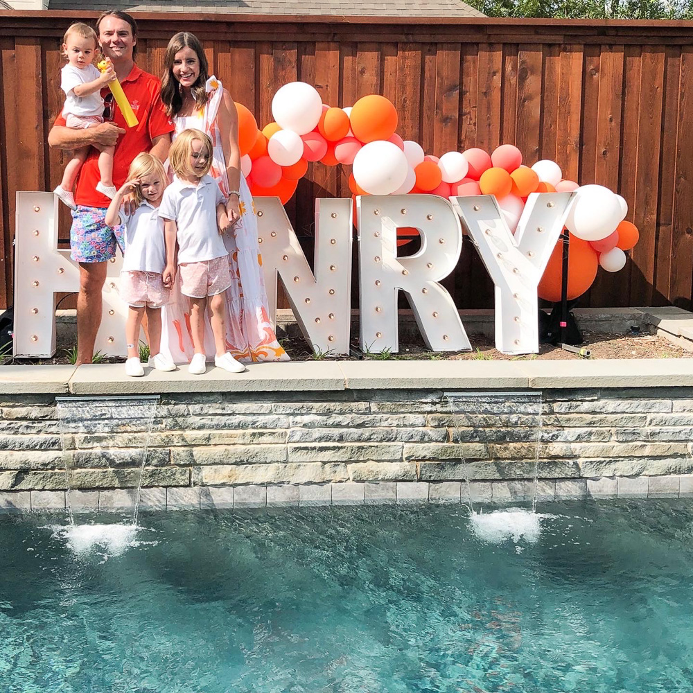 family standing by henry light up sign with orange balloons