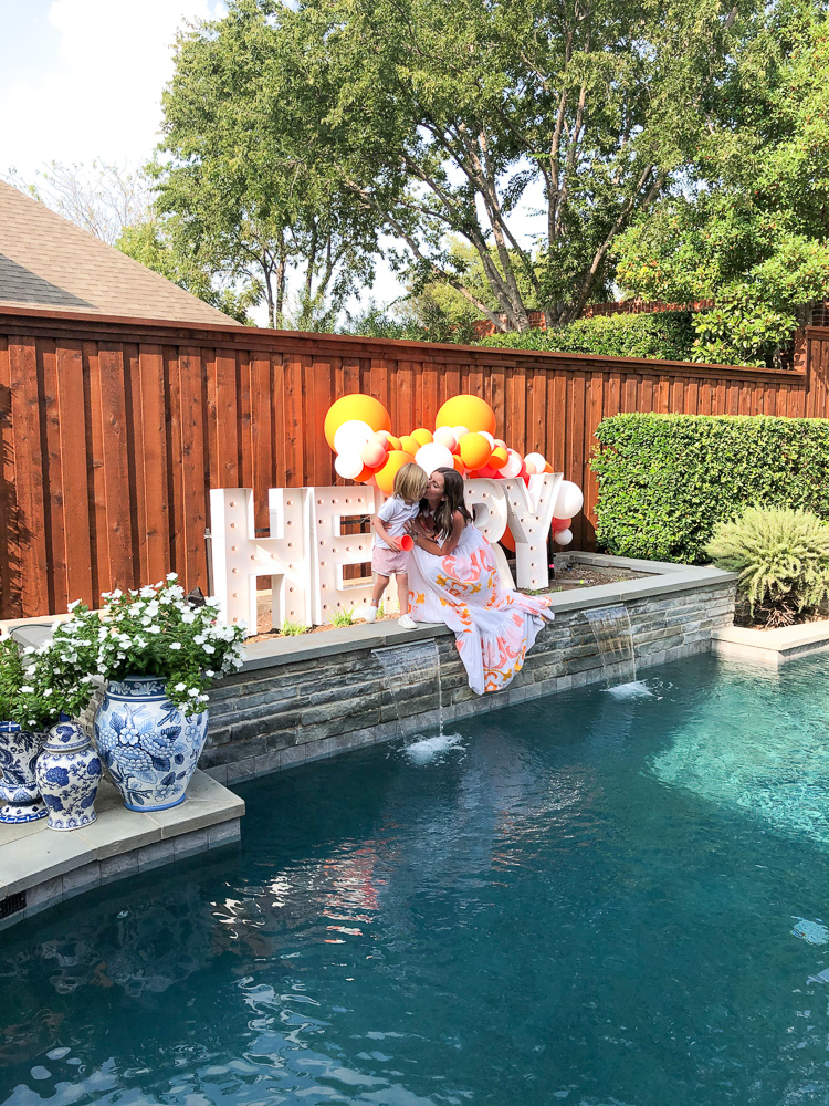 henry light up sign by swimming pool with mom and toddler boy