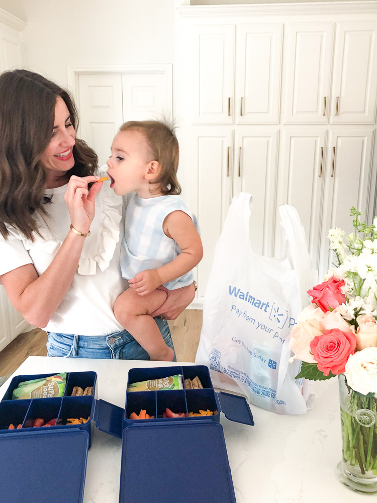 mom holding baby while making pre-school lunches