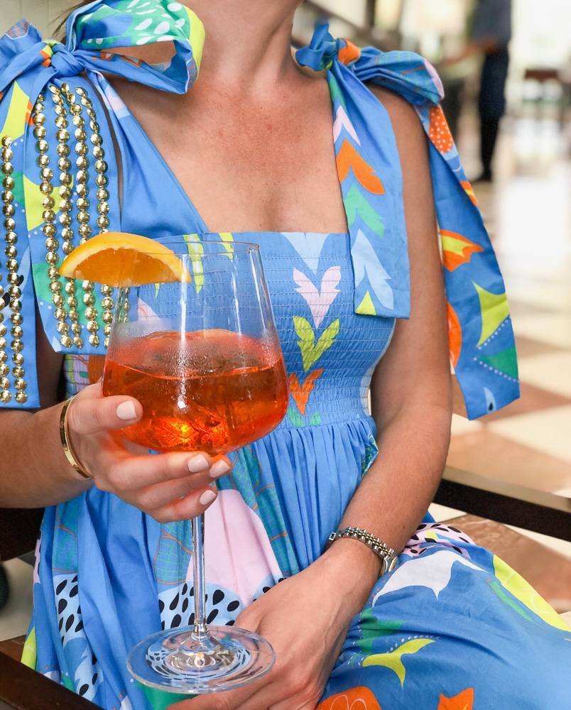 colorful dress with bows woman holding orange cocktail