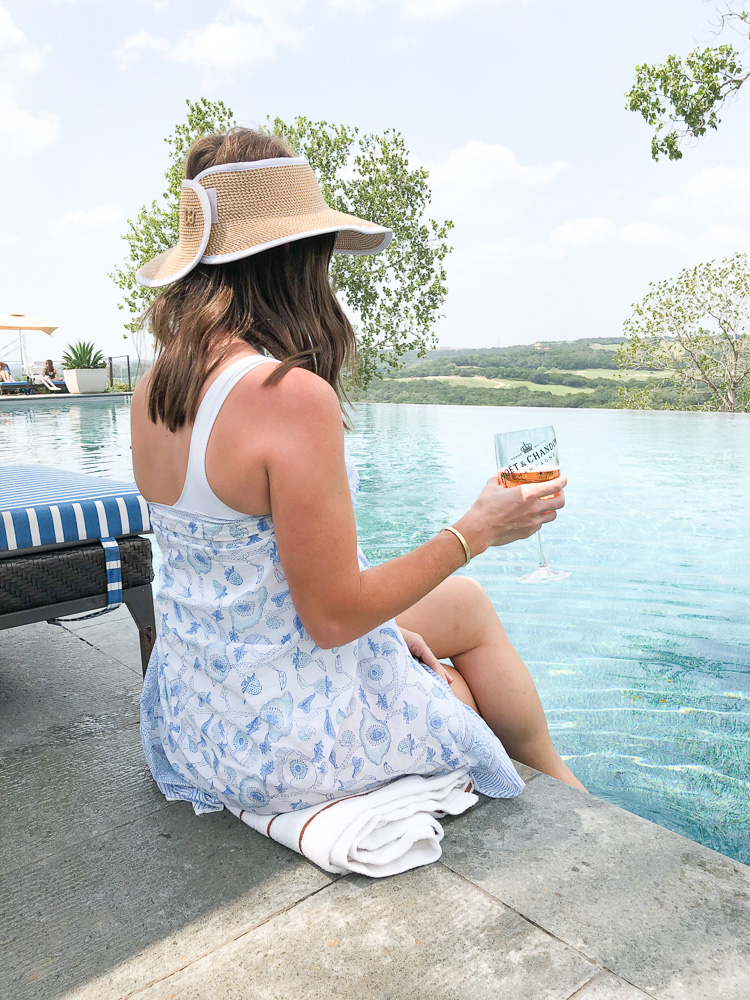 woman sitting by pool with champagne