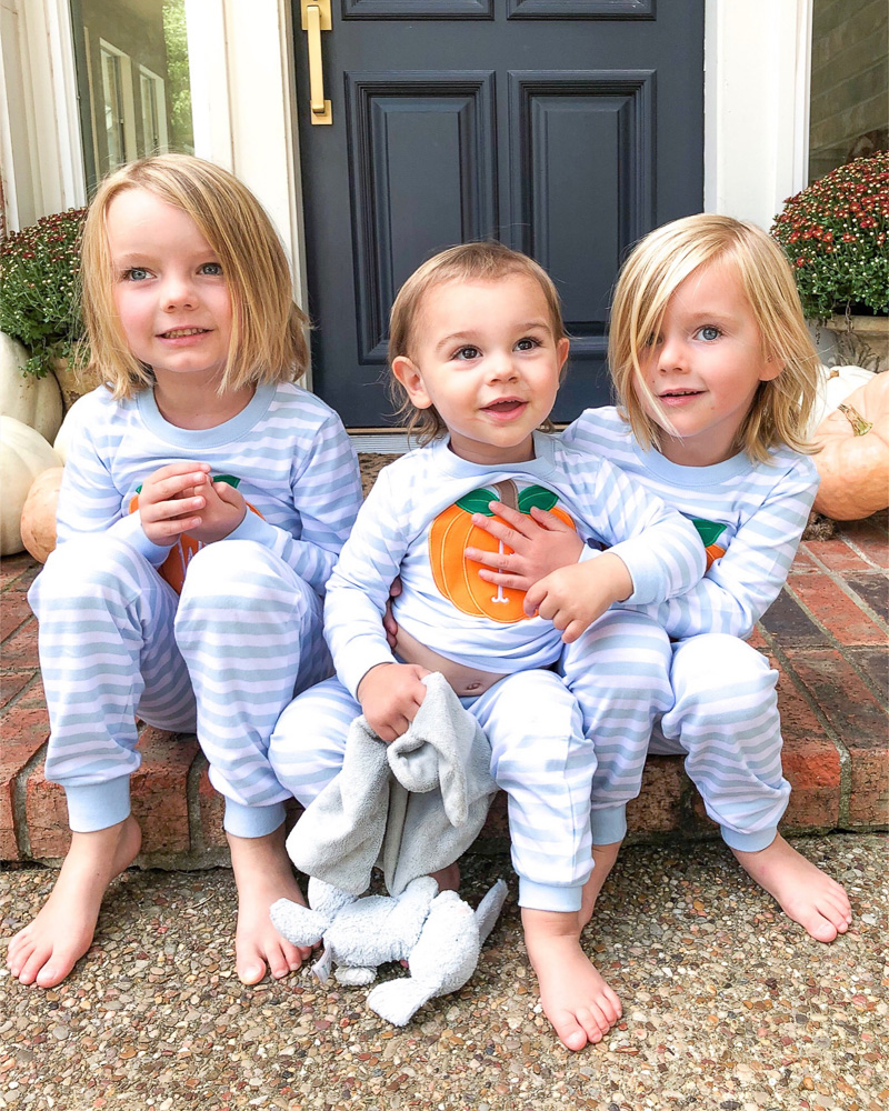 three toddler brothers sitting on front porch in pumpkin pajamas