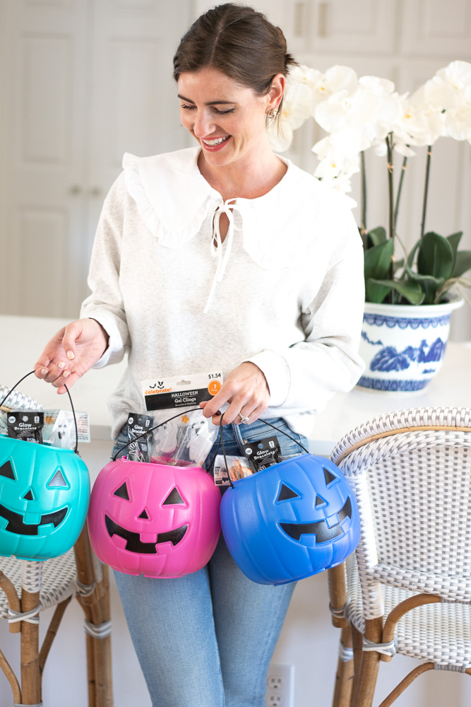 woman holding three colorful pumpkin pails