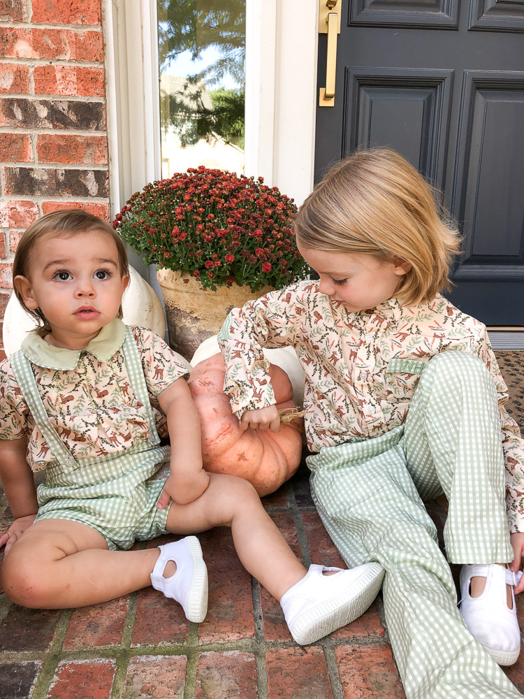 toddler brothers in thanksgiving outfits sitting by pumpkin