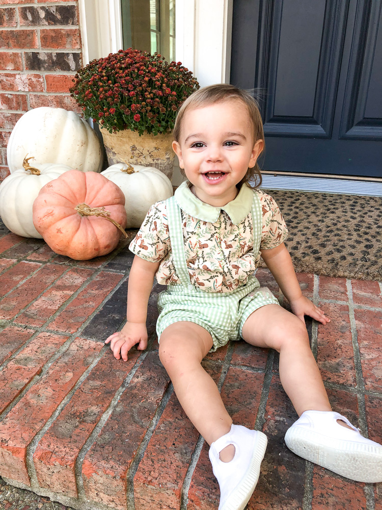 baby boy wearing thanksgiving outfit sitting on porch