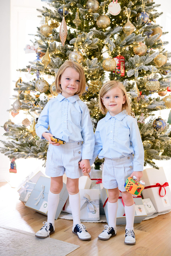 two brothers standing in front of christmas tree