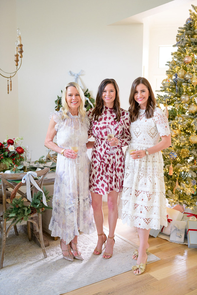 three women standing in front of Christmas tree