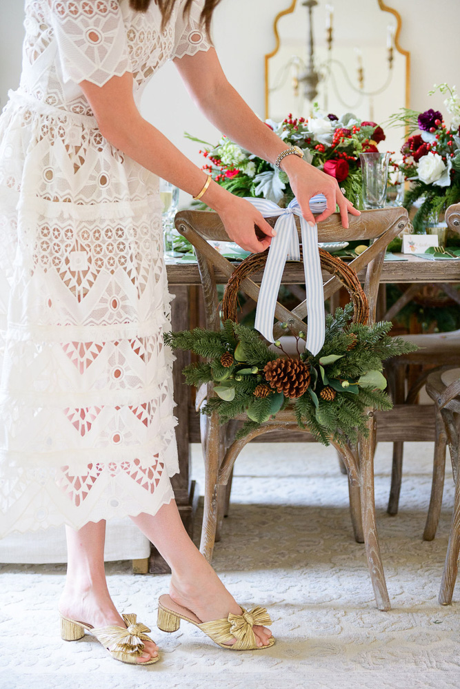 tying bow to chair back wreath