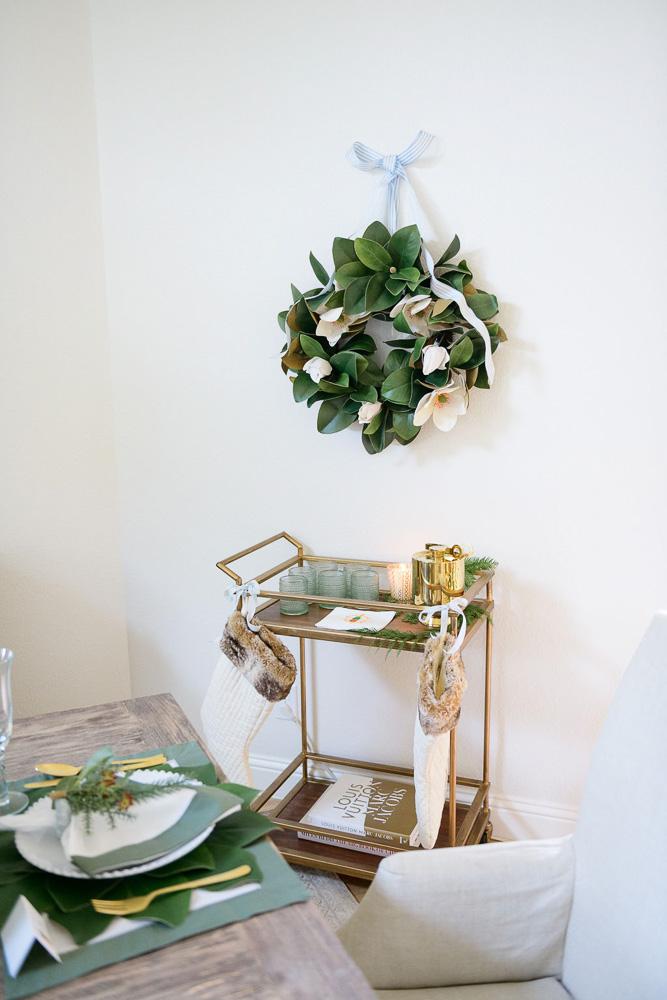 magnolia wreath hanging over bar cart