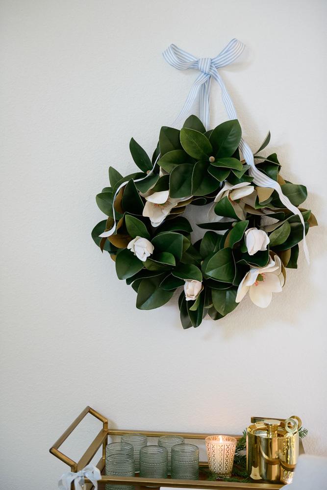 magnolia wreath hanging above bar cart