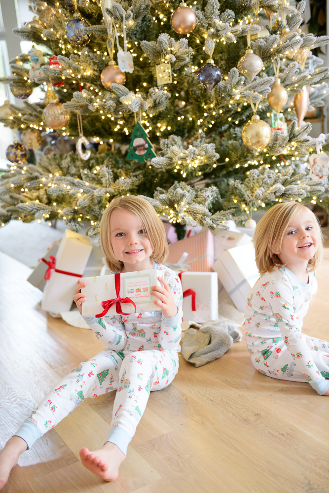 two brothers in matching christmas pajamas in front of christmas tree