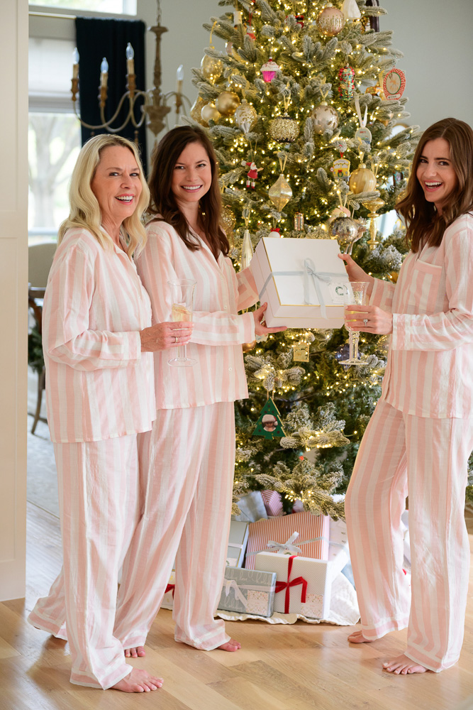 three women in matching pink striped pajamas with gift box