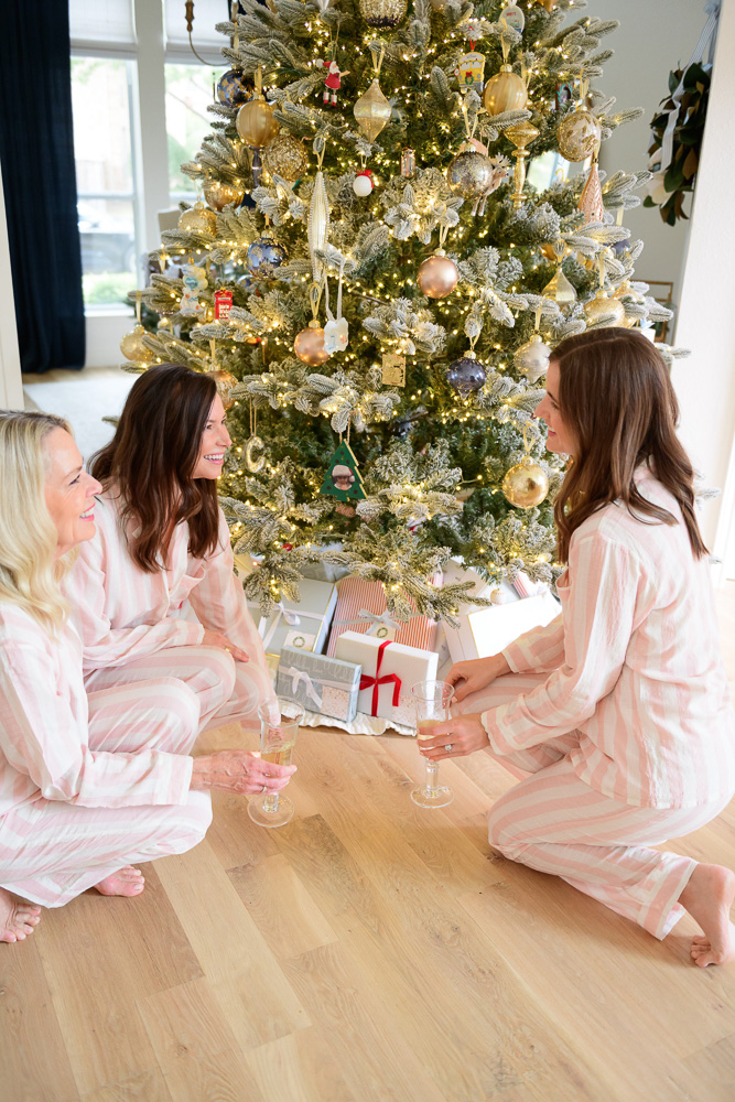 three women sitting on the floor in front of christmas tree in matching pajamas