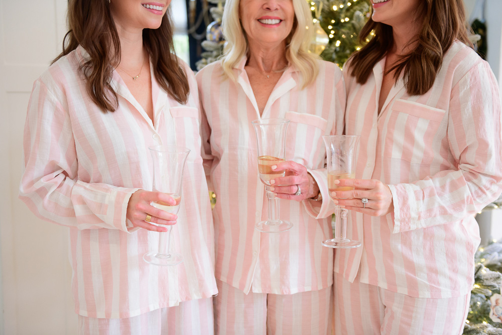 three women in matching pink striped pajamas drinking champagne