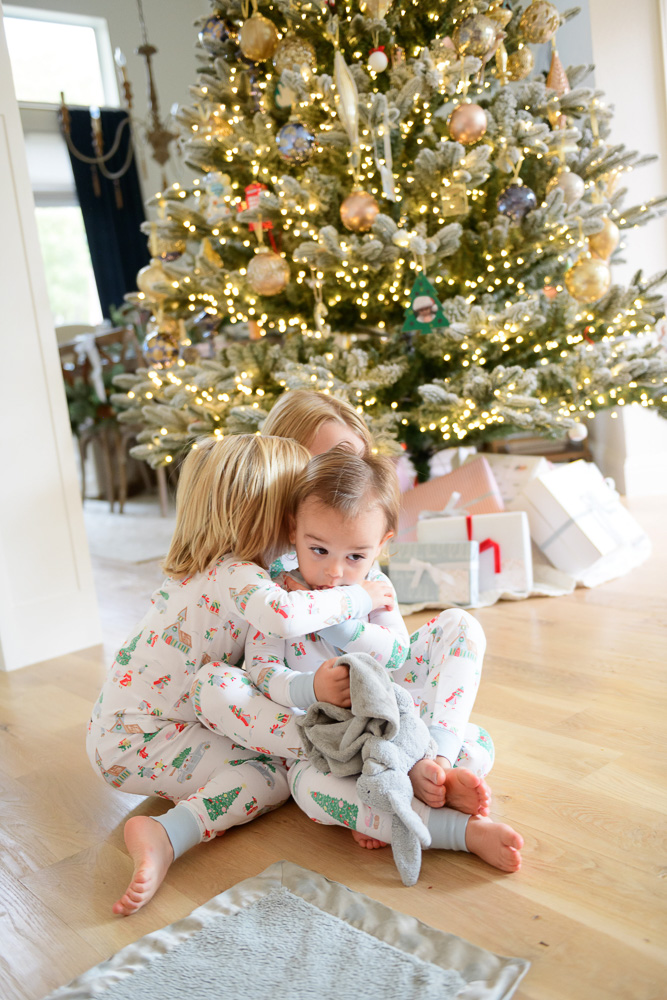 three toddler boys cuddling in front of christmas tree