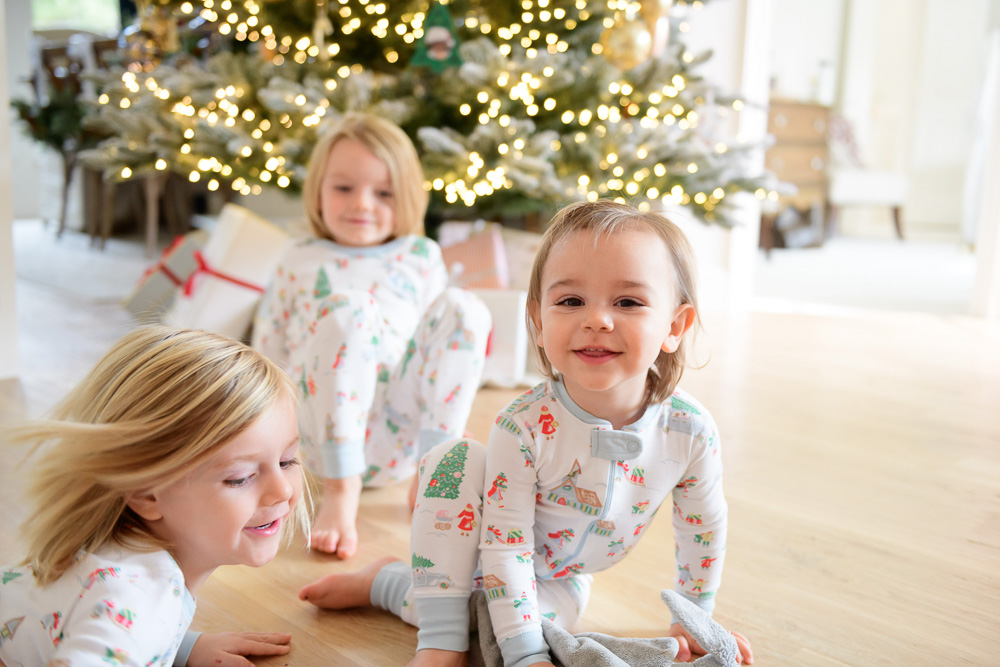 three toddler boys playing in front of christmas tree