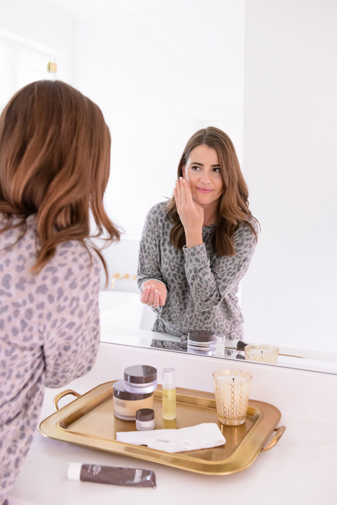 woman looking in mirror while finishing skin care routine