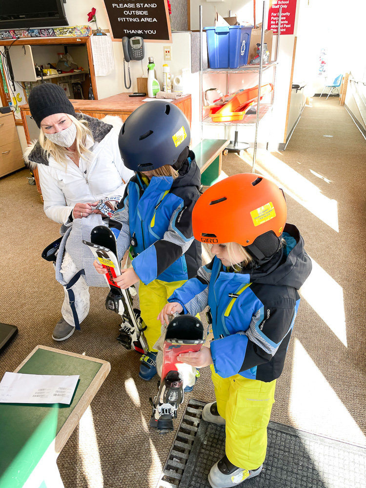 toddler boys being fitted for ski rentals