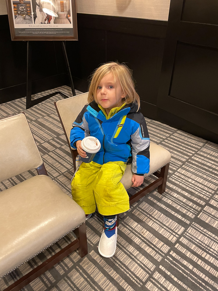 toddler drinking hot cocoa at four seasons vail ski concierge
