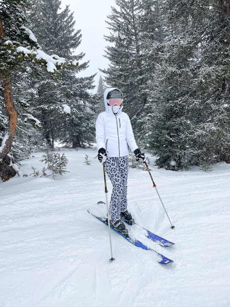 skier in leopard ski pants white jacket