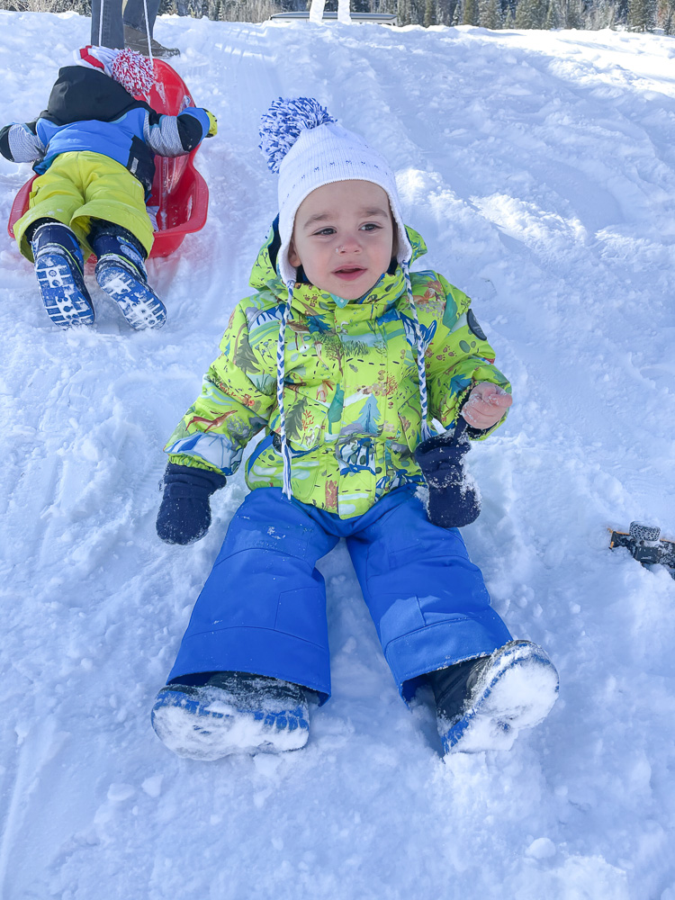 baby boy sliding down snowy hill