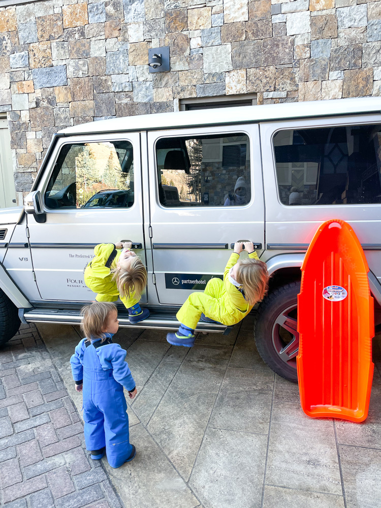 three boys hanging on mercedes house car at four seasons vail