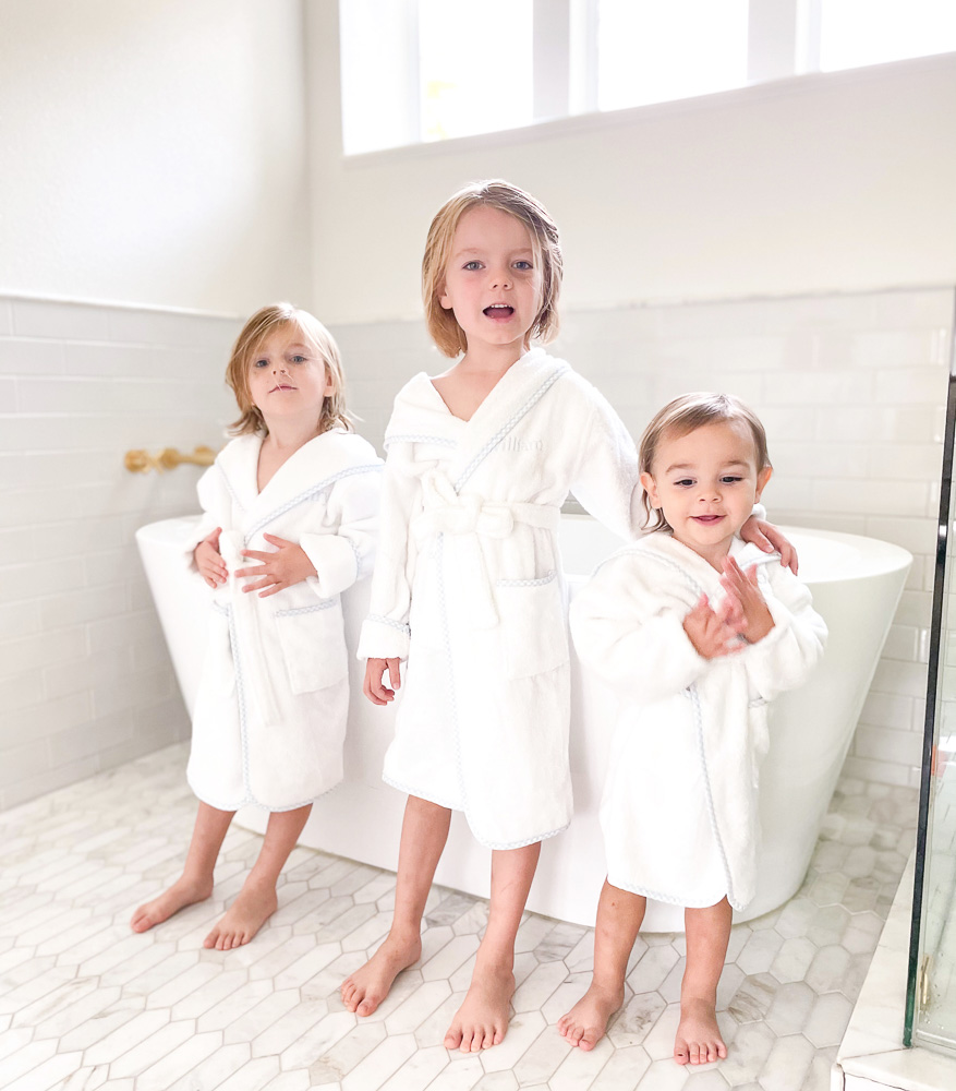 three brothers in white bath robes by bathtub