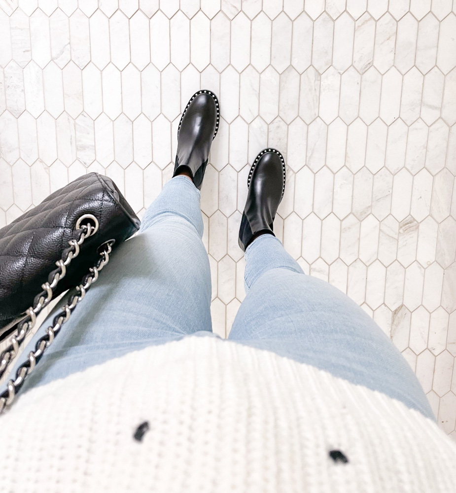 white sweater blue jeans black boots black handbag