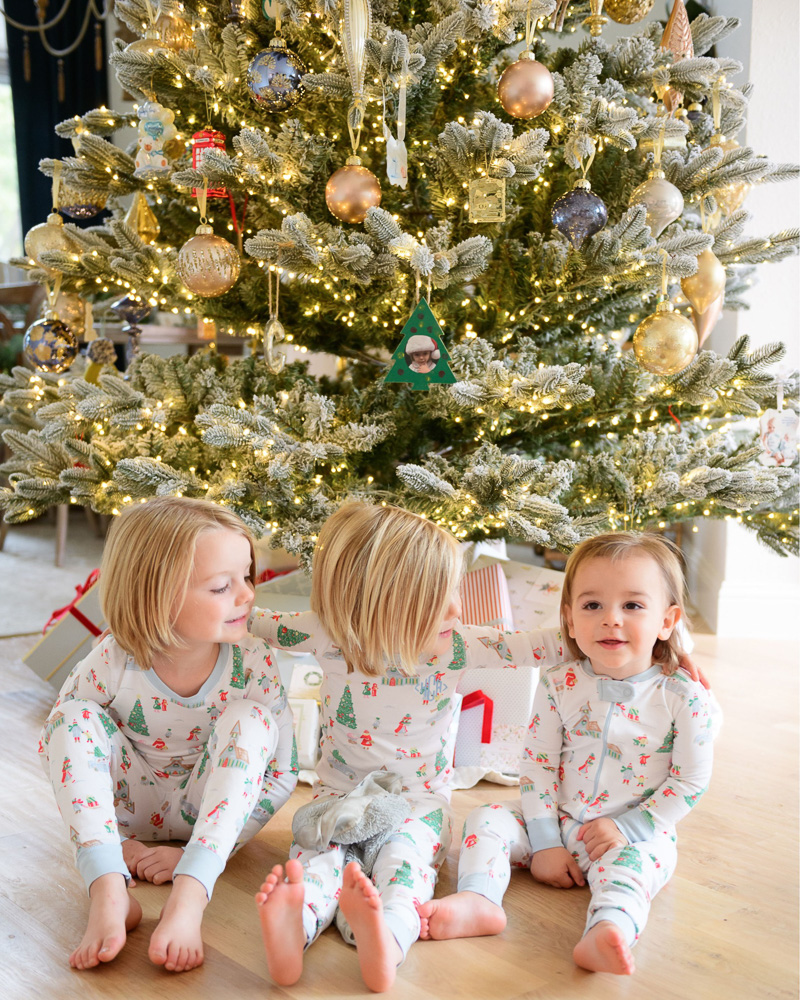 three toddler brothers in matching pajamas in front of Christmas tree