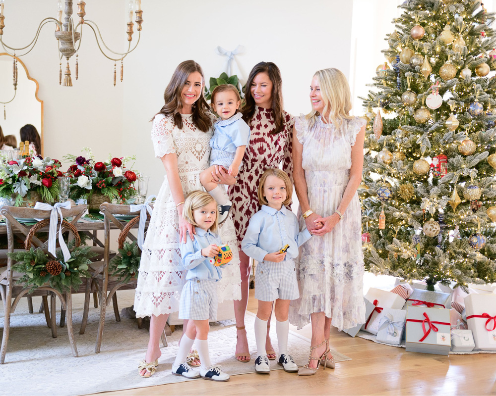 three women with three toddler boys in front of Christmas tree