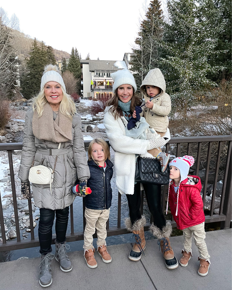 two women with three toddler boys on bridge bundled up for winter over river